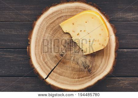 Piece of gouda herb cheese on natural wood disc on rustic background, still life, top view