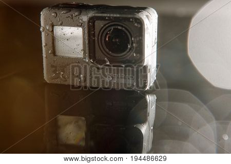 Kharkov, Ukraine - April 13, 2017: GoPro HERO 5 digital action camera with water drops with lensflare on black. Compact gadget waterproof , support 4k video and is often used in extreme photography