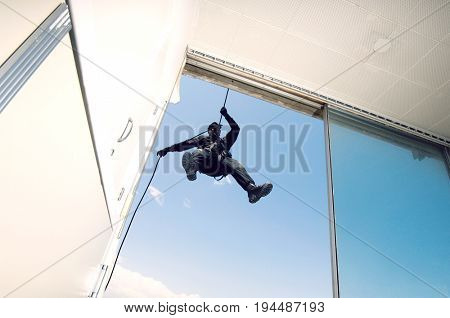 Low angle view of a mature military man rappelling down the rope from building