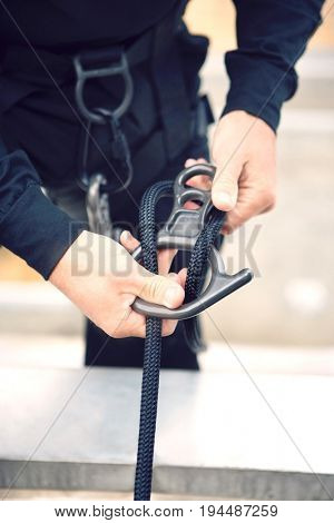 Close up of a man's hand fixing rope in harness