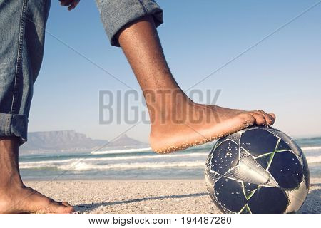 Closeup side view of barefeet with soccer ball at beach