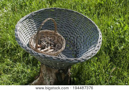 Big old weathered empty wicker laundry basket and small basket full of wooden clothes pegs on wooden log on green grass country garden meadow