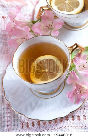 flavored tea in a white porcelain bowl and a pink flower freesia