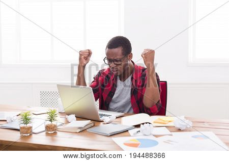 Disappointed black businessman in office, in casual, work with laptop, solving a problem