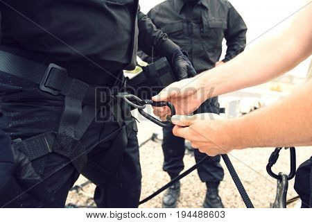 Close up of man's hand fixing harness on commando's waist with partner standing in the background