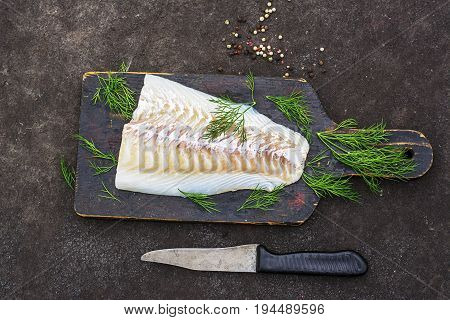 Raw cod before cooking on a black chopping Board with herbs and sea salt on a dark background. Top view.