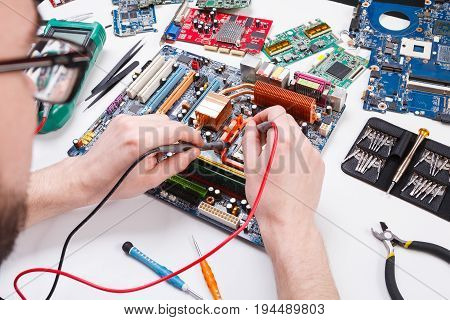 Engineer checking motherboard with multimeter close up. Computer diagnostic, maintenance support and repairing service concept.