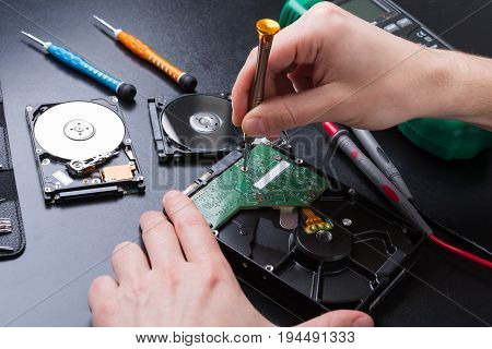 Hard disc drive disassembling close up. Repairman opening hdd for recovery information, service center and electronics repair concept.