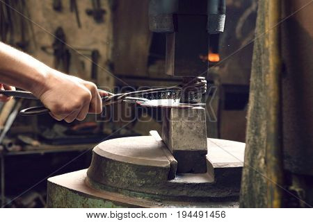 Young male blacksmith shaping metal in workshop