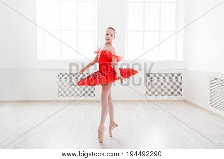 Young teenager ballerina practicing classical dance pas in studio before performance. Ballet student exercising in ballet costume, standing on her toes.