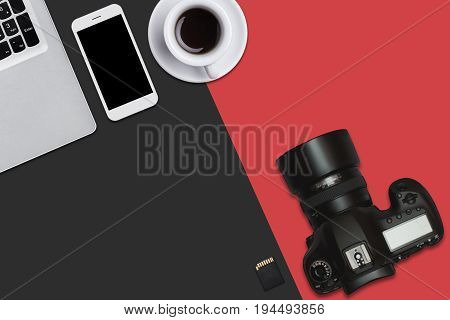 Top View Of Laptop, Smart Phone, Flash Card, Camera And Cup Of Coffee Lying On Red And Black Surface