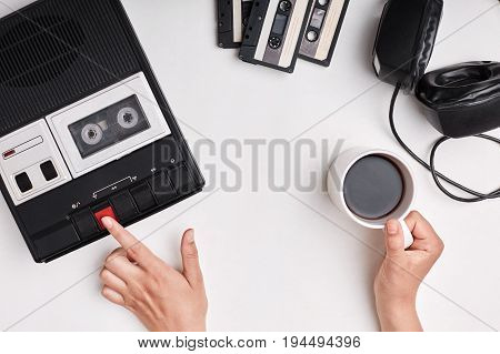 Top View Of Retro Tape Recorder, Cassettes And Headpnones Lying On White Surface. Woman`s Hands Swit