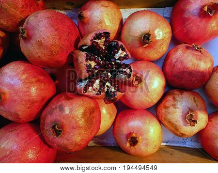 Group of pomegranates in the box at market. Pomegranate in the middle is cut to show seeds inside.