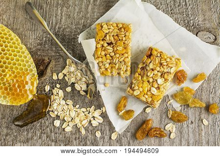Organic oat cereal bars with honey and Golden raisins on a simple wooden background. Top view.