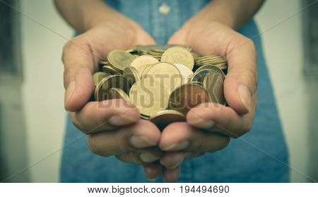 Male holding money gold coins in her hand for financial and saving money concept.
