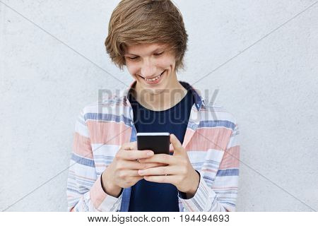 Cheerful Teenager With Trendy Hairstyle Holding Modern Smart Phone Typing Messages Or Playing Games