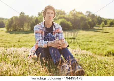 Handsome Guy With Trendy Hairstyle Wearing Shirt And Jeans Sitting On Green Grass Of Meadow Relaxing