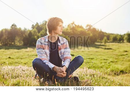 Serious Thoughtful Boy In Casual Clothes Sitting Crossed Legs On Green Grass Looking Aside With Drea