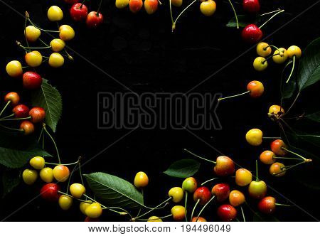 Sweet fresh cherries background. Scattered cherries on dark rustic wood pattern with copy space. Cherry fruit backround. Garden fresh organic cherries at wooden table top view. Food background.