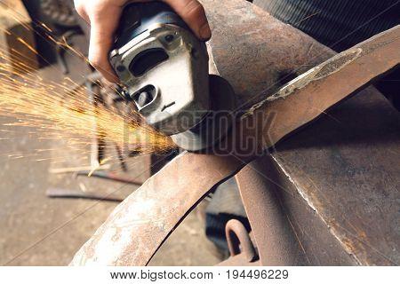 Blacksmith using angle grinder on edge of metal tool in workshop