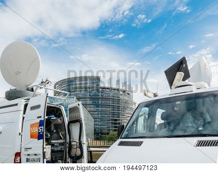 STRASBOURG FRANCE - JUN 30 2017: TV Media Television Trucks with multiple equipment Satellite parabolic antennas and fiber optic cables preparing to report live the official European Ceremony of Honour for Dr. Helmut Kohl at European Parliament