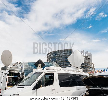 Debate preparation for plenary session: TV Media Television Trucks with multiple Satellite parabolic antennas and fiber optic cables preparing to report live the official European Ceremony
