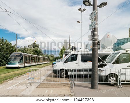 STRASBOURG FRANCE - JUN 30 2017: Tramway passing near TV Media Television Trucks with multiple Satellite parabolic antennas and fiber optic cables preparing to report live the official European Ceremony of Honour for Dr. Helmut Kohl at European Parliament