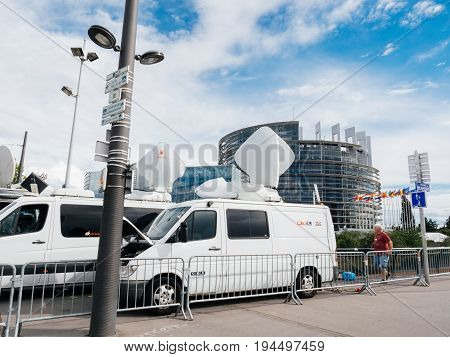 STRASBOURG FRANCE - JUN 30 2017: RTL NTV TV Media Television Trucks with multiple Satellite parabolic antennas and fiber optic cables preparing to report live the official European Ceremony of Honour for Dr. Helmut Kohl at European Parliament