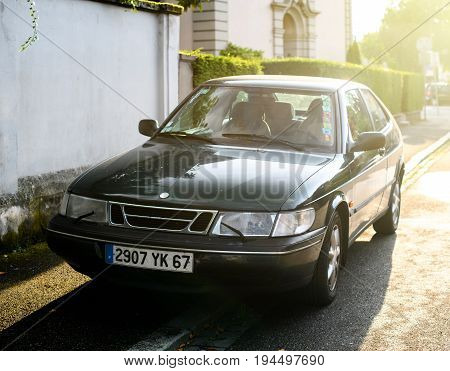 STRASBOURG FRANCE - MAY 2017: Saab 900 a compact luxury automobile which was produced by Saab from 1978 until 1998 in two generations beautiful sun flare light behind