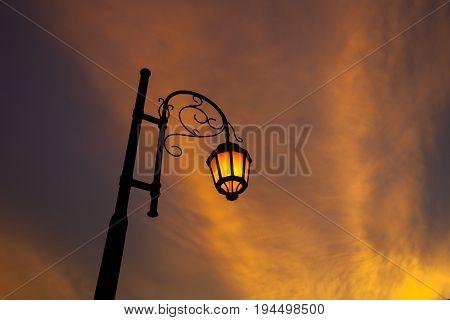 Vintage illuminated street lamps orange light with sunset cloud orange color background