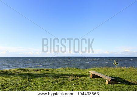 Wood made bench on a grass field near sea