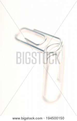 Two silver paper clips on white background