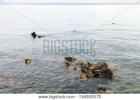 Rocks In Water Near Waterfront In Giardini Naxos