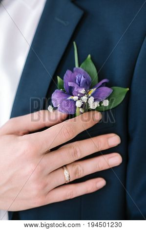 graceful stylish buttonhole of the groom from a iris closeup.