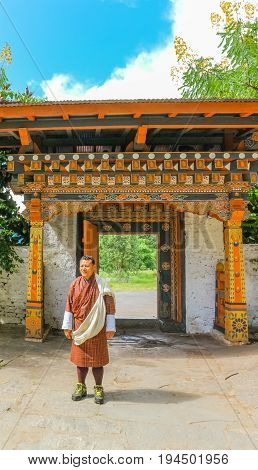 Paro Bhutan - September 10 2016: Local Bhutanese tourist guide wearing traditional clothing standing in front of the door in Kichu Lhakhang temple. The monastery is one of the oldest and sacred temples in Bhutan.
