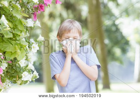 Allergy. Child is blowing nose with tissue paper at the park