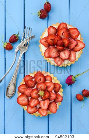 Sweet tarts with fresh strawberries mascarpone served with vintage forks on blue table vertical