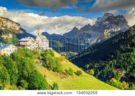 Stunning alpine spring landscape with church on the Santa Lucia pass and Pelmo mountain group in background Colle Santa Lucia Dolomites Italy Europe