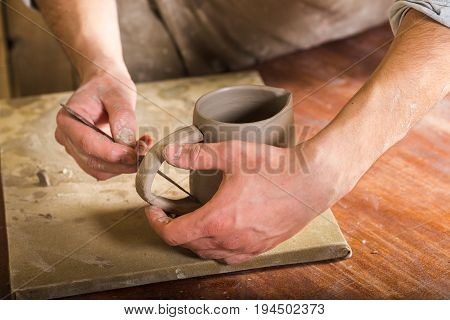 pottery, stoneware, ceramics art concept - closeup on craftsman hands connecting handle to cup with tool, master fingers works with pieces of fireclay, young male stands at a workshop behind the table
