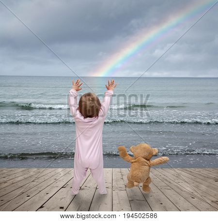 small child and a teddy bear watching rainbows