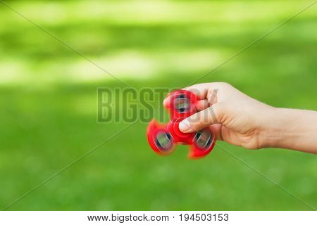 Child hand with red spinner. Close up