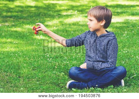 Child with spinner sitting on the grass