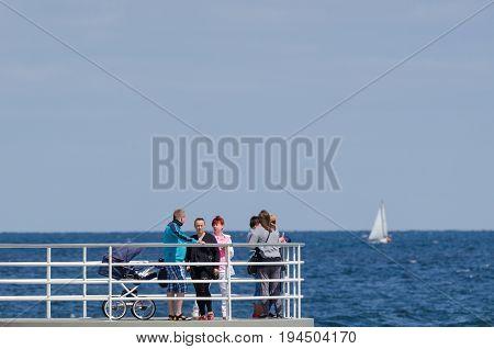 KOLOBRZEG, WEST POMERANIAN / POLAND - Holidaymakers walk the pier