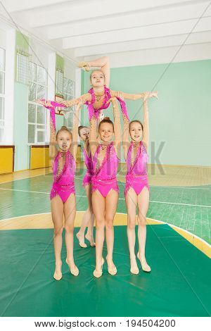 Group rhythmic gymnasts, 11-12 years old girls carrying out their routine in school gymnasium