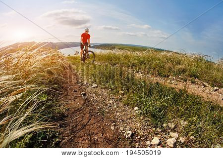Young cyclist riding the mountain bike on the beautiful summer trail in the countryside against sky with clouds. Sportsman dressed in the sportwear, with helmet, sunglasses and backpack. Horizontal photo and fisheye. Concept of the healthy lifestyle.