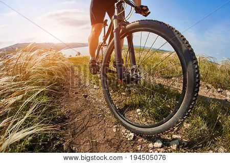 Young cyclist riding mountain bicycle through green meadow against beautiful sky. Attractive sportsman in the black sportwear, with helmet and backpack. Healthy and active lifestyle concept
