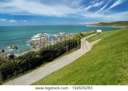 A footpath along the coast in Woolacombe. People on the bench sit and enjoy the scenery. North Devon. England