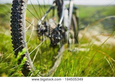 Close-up of the wheel of mountain bicycle in the green grass in the meadow in the countryside. Detail of the mountain bike. Horizontal photo. Sportive backgrounds and still-life. Travel in the countryside. Concept of the healthy lifestyle.