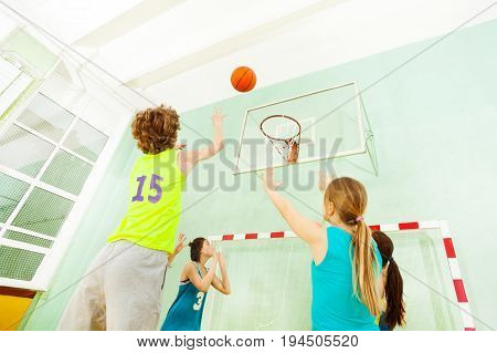 Low angle view of boy jumping and throwing the ball into the basket during basketball match in sports hall