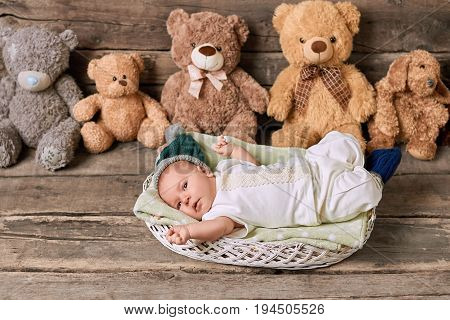 Basket, infant and teddybears. Little kid on wood background. What do babies need.